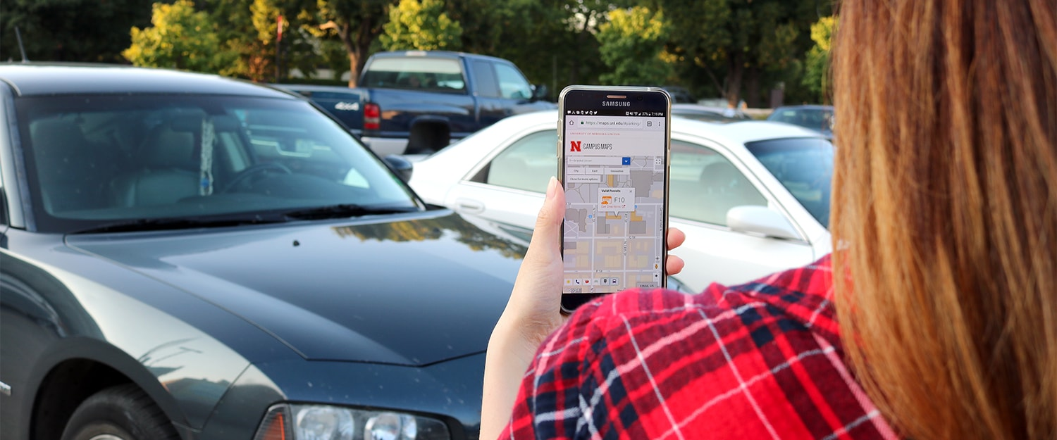 Lady looking for parking lot using Campus Maps app on smart phone